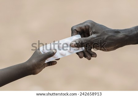 Curing Disease Symbol: African Black Man Giving Pills to Child - stock photo