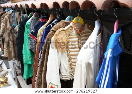 Curiosity shop. Various vintage clothing hanging on hangers outdoor - stock photo