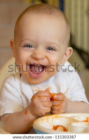 curious and playful baby boy examines and eating an apricot - stock photo