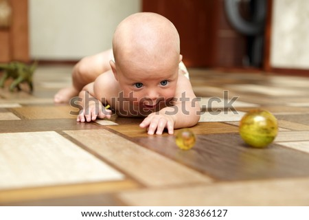 Curious baby playing with ball on a floor - stock photo