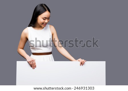 Curious beauty. Beautiful young Asian woman looking at copy space and smiling while standing against grey background - stock photo
