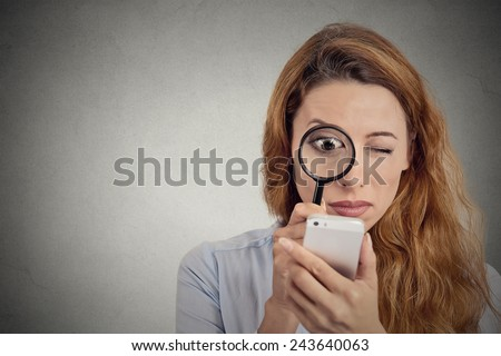 Curious. Business woman looking through magnifying glass on smart phone screen isolated grey background. Human face expression. Investigator searching. Security safety concept. Complicated technology - stock photo