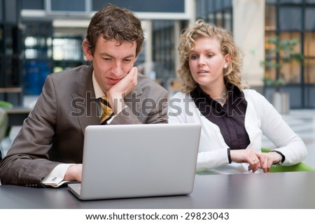 Curious businesswoman looks what her colleague is doing on his laptop. - stock photo