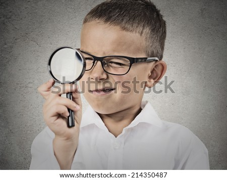 Curious child, boy looking through a magnifying glass, isolated grey wall background. Curiosity concept. Face expressions, life perception, discovery - stock photo