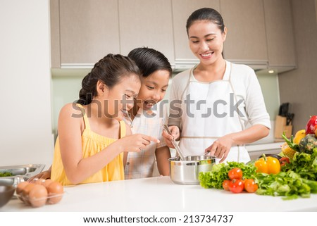 Curious children looking into saucepan in hands of their mother - stock photo