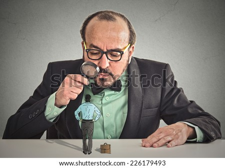 Curious corporate businessman skeptically meeting looking at small employee standing on table through magnifying glass isolated office grey wall background. Human face expression, attitude, perception - stock photo