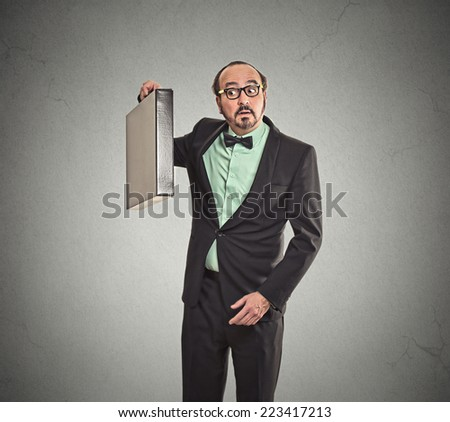 Curious funny looking business man guessing what inside his new briefcase gift box isolated grey wall background. Human face expressions, emotions, body language - stock photo
