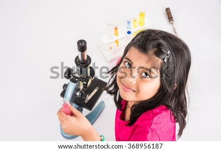 curious indian girl with microscope, asian girl with microscope, Cute little girl holding microscope, 4 year old indian girl and science experiment, girl doing science experiments, science lab - stock photo