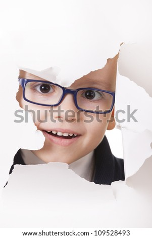 Curious kid in spectacles looks through a hole in white paper - stock photo