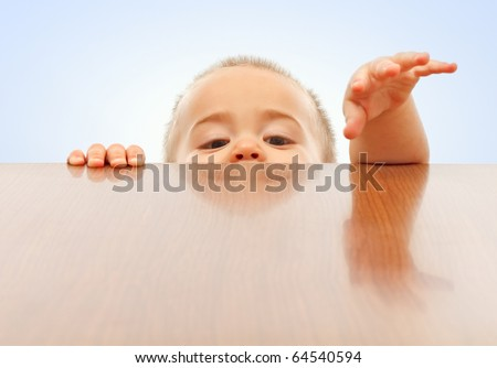 Curious little boy looking up and raising hands onto table surface - stock photo
