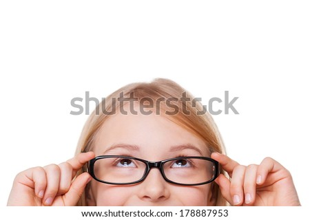 Curious little girl. Cropped image of cheerful little girl adjusting her glasses and looking up while isolated on white - stock photo