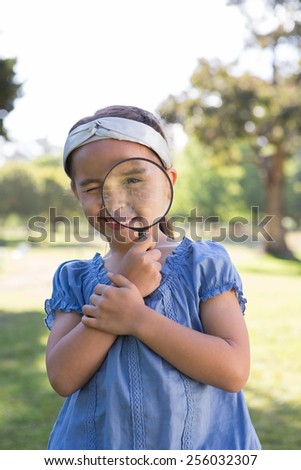 Curious little girl looking through magnifying glass on a sunny day - stock photo