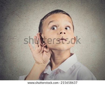 Curious man, boy, listens. Closeup portrait child hearing something, parents talk, hand to ear gesture isolated grey wall background. Human face expression, emotion, body language, life perception - stock photo