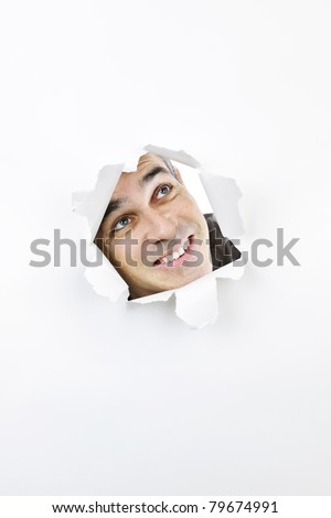 Curious man looking up through hole ripped in white paper - stock photo