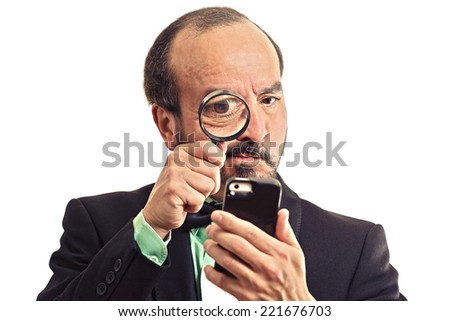 Curious. Mature business man looking through a magnifying glass on smart phone isolated  white  background. Human face expression. Investigator looking with magnifying glass. Security safety concept - stock photo