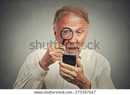 Curious. Portrait senior man investigator looking through magnifying glass at smart phone isolated grey wall background. Human face expression. Security safety or bad vision concept - stock photo