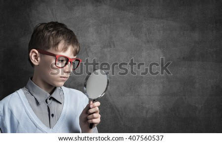 Curious school boy with magnifier - stock photo