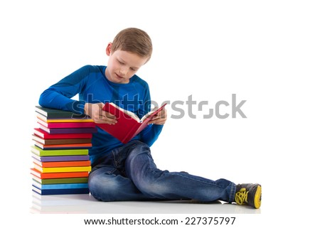 Curious schoolboy reading a book. Schoolboy sitting on the floor close to the stack of books and reading one of them. Full length studio shot isolated on white. - stock photo