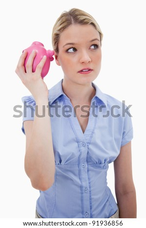Curious woman shaking piggy bank against a white background - stock photo
