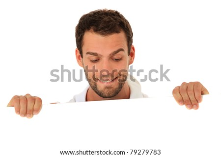 Curious young guy behind white wall. All on white background. - stock photo