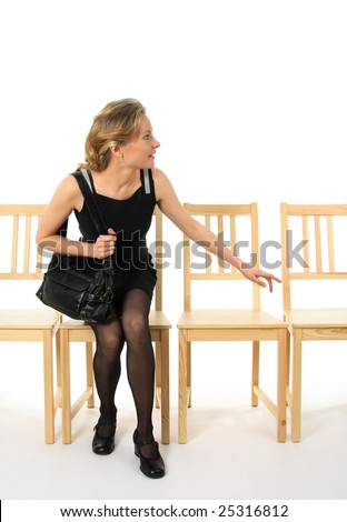 Curious young lady getting up from a chair and looking. - stock photo
