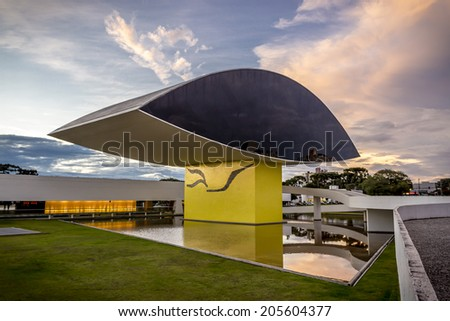 CURITIBA, BRAZIL - MARCH 20: Panoramic view of Oscar Niemeyer Museum in Curitiba, PR, Brazil at sunset showcasing its main entrance and its eye-shaped sculpture on March 30, 2014. - stock photo