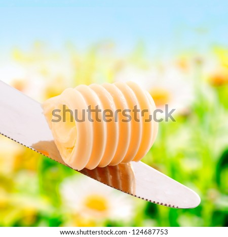 Curl of fresh summer butter in a spiral roll balanced on a silver knife outdoors in summer sunshine with greenery - stock photo