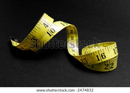 Curled yellow measuring tape on black background. - stock photo