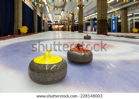 Curling stone on ice of a indoors rink - stock photo
