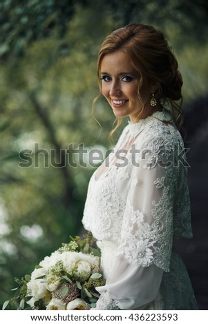 Curls lie around pretty bride's face while she poses in the garden - stock photo
