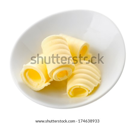 Curls of fresh butter in bowl, isolated on white - stock photo