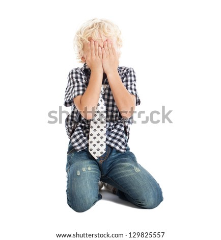 Curly blond boy sitting on the floor, covering his face with his hands. Crying boy. Studio shot, isolated on white background. - stock photo