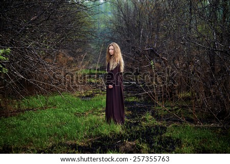 Curly blond young woman in nature - stock photo