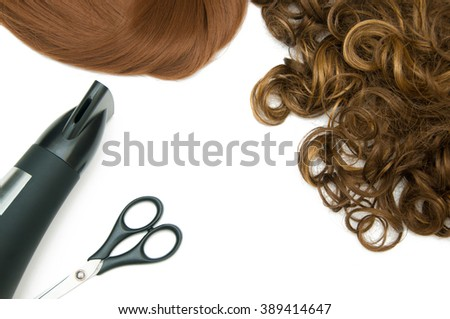 Curly brown hair and red straight hair with hair dryer and scissors isolated on white - stock photo