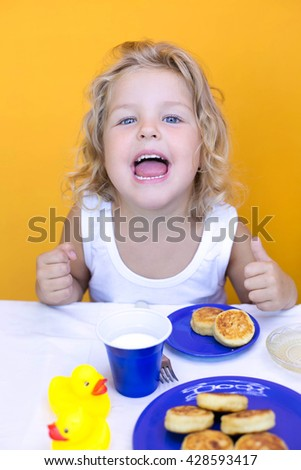 curly girl eating delicious cheesecakes morning cute little girl with a fork and cheese cakes on a yellow background - stock photo