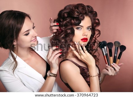 Curly hair. Beauty makeup. Professional artist woman applying make up sensual brunette girl model with red lips and shiny healthy hairstyle. - stock photo