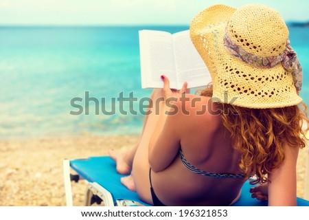 Curly hair female reading a book on the beach. - stock photo