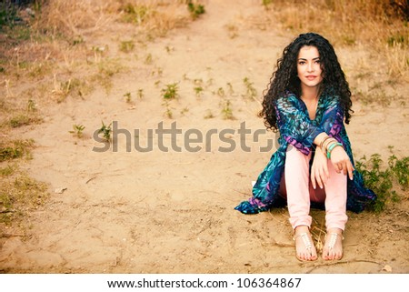 curly hair smiling woman in colorful dress sit on ground full body shot outdoor summer day - stock photo