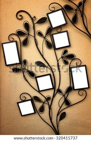 Curly iron picture holder with 6 empty frames leaning on a yellow wall - stock photo