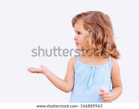 Curly little girl holding her hand out and showing copy space for your product - stock photo