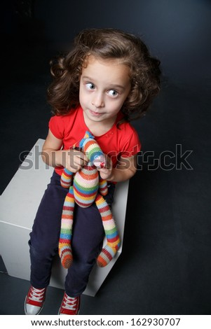 Curly little girl hugs her plush toy - stock photo