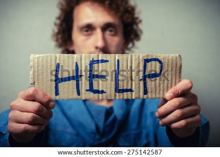Curly man with a kraft cardboard with text donate help. On a gray background. - stock photo