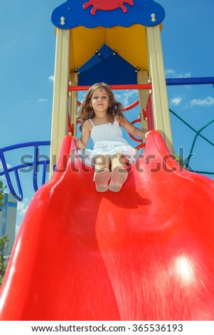 Curly preschool girl sitting on the top of a kids slide, at the playground  - stock photo