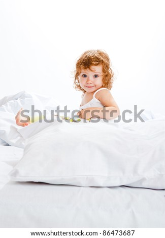 Curly toddler girl in bed, looking into camera - stock photo