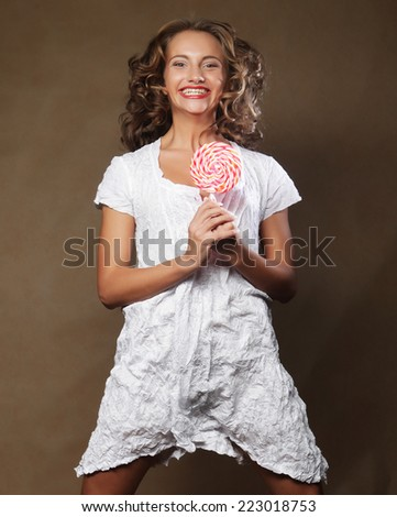 curly woman with lollipop over brown background - stock photo