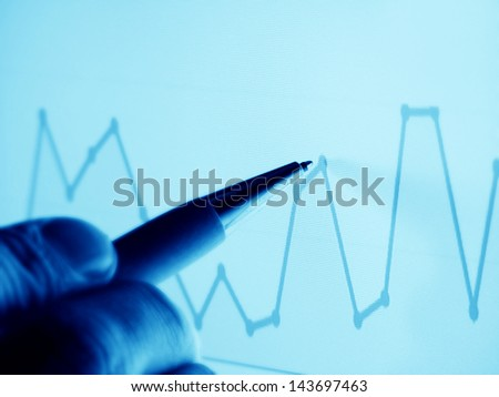 Currency data on a computer screen and pen in arm - stock photo