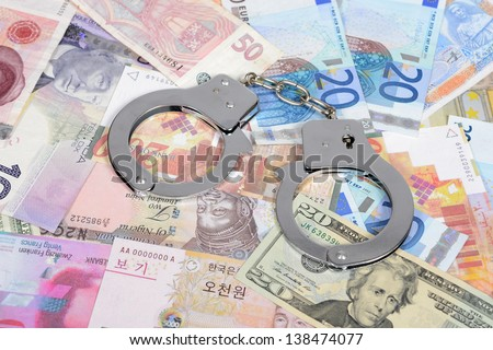 Currency from world with handcuffs - stock photo