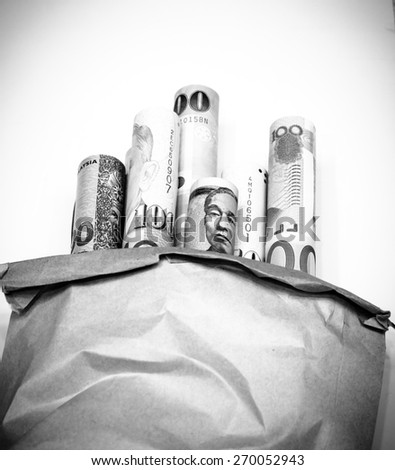 Currency,money roll put in paper bag on black and white color.Focus on currency roll ,blurry on paper bag - stock photo