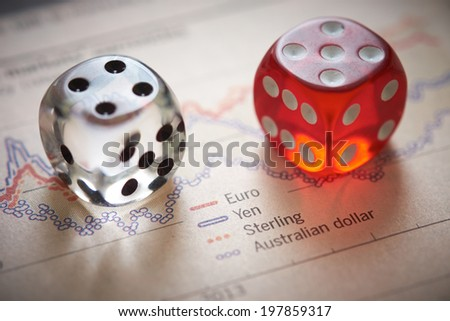 Currency trading. Coloured dice on top of the financial section of a newspaper. - stock photo