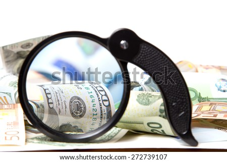 Currency under a magnifying glass on white background - stock photo